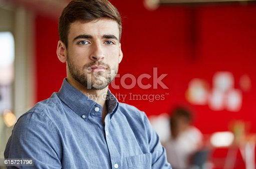 istock Confident male designer working in red creative office space 615721796