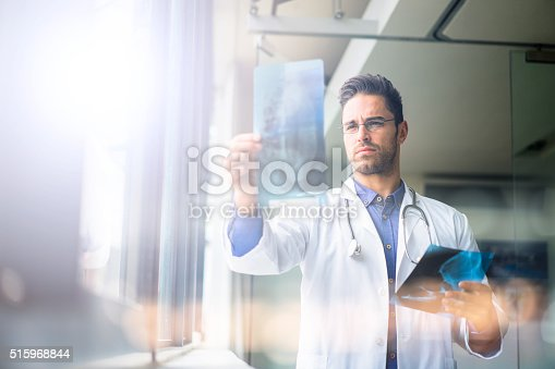 istock Confident male doctor examining x-ray in hospital 515968844