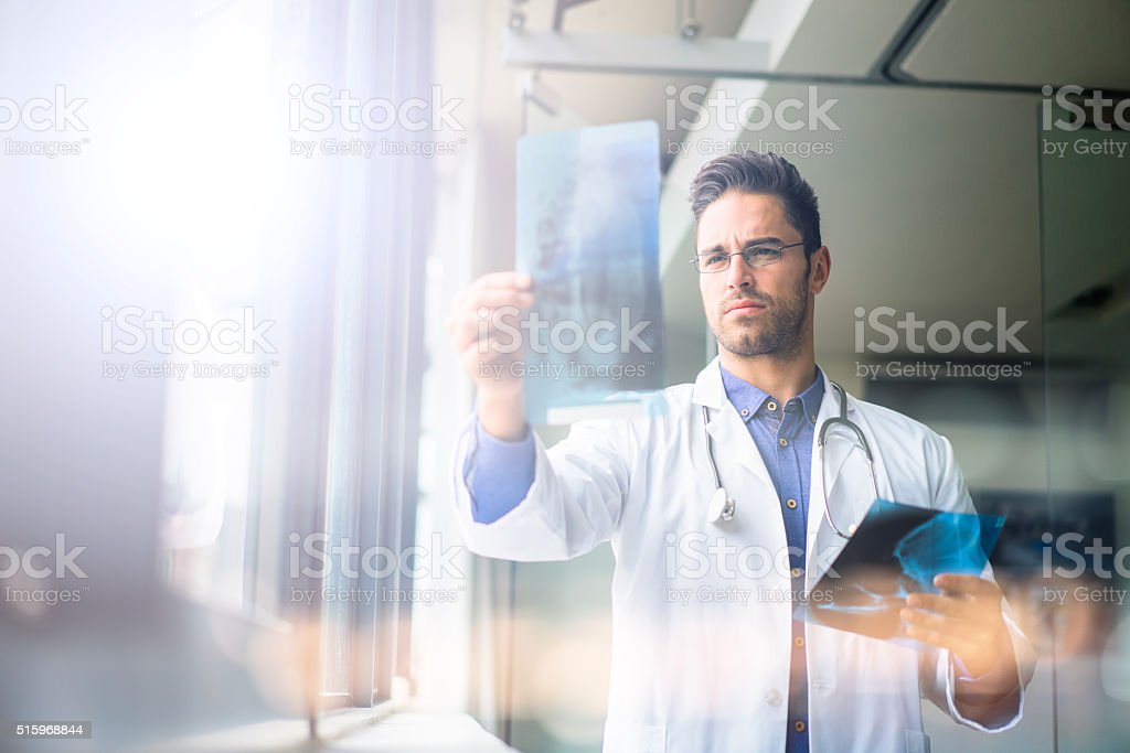 Confident male doctor examining x-ray in hospital stock photo