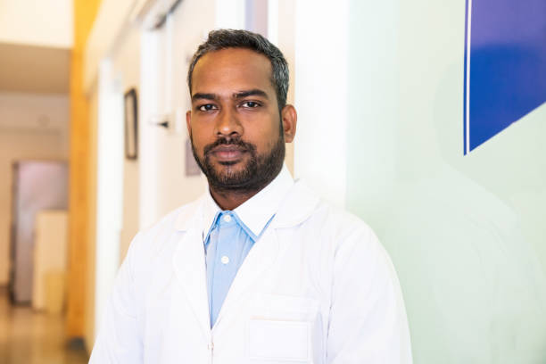 Confident male doctor standing in medical center Portrait of confident doctor in hospital. Male healthcare worker is in corridor of medical center. He is wearing lab coat. indian male stock pictures, royalty-free photos & images