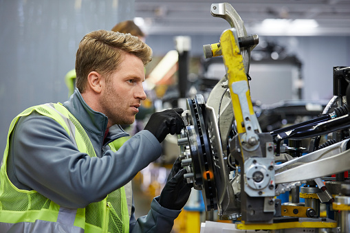 istock Confident male engineer examining car chassis 941796726
