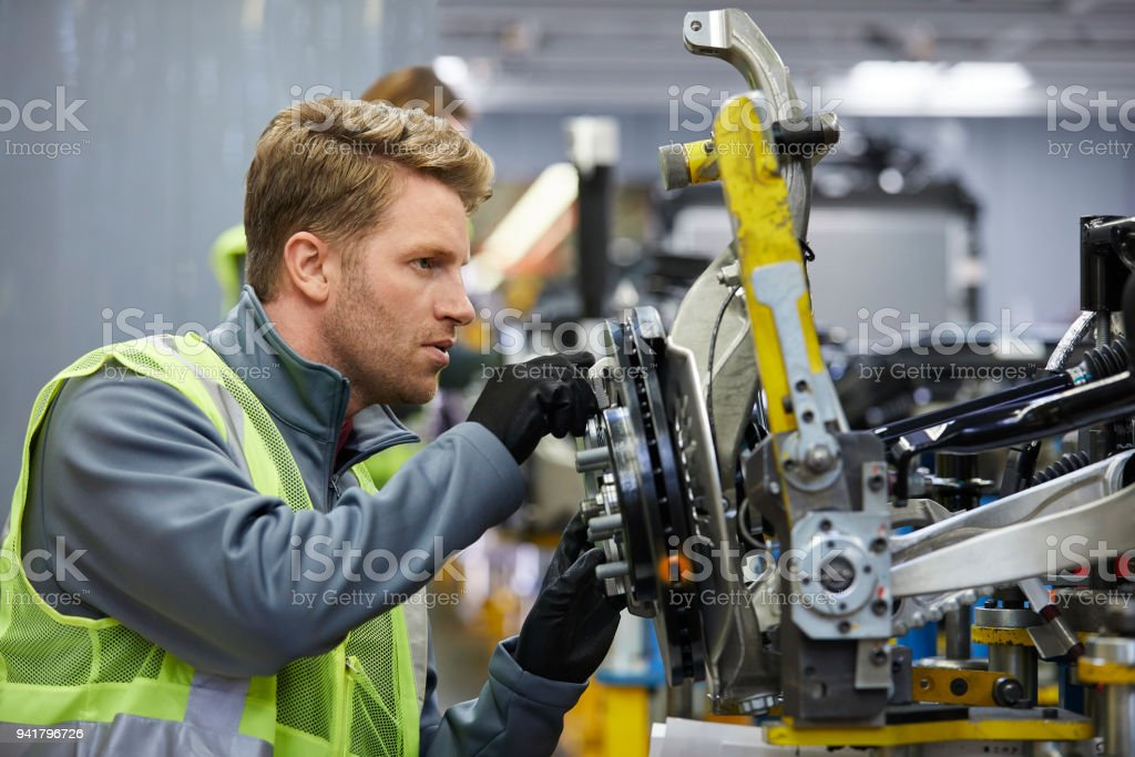 Confident male engineer examining car chassis stock photo