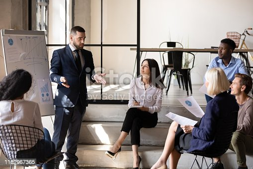 1031235468 istock photo Confident male executive coach speaking to employees group during workshop 1182967365