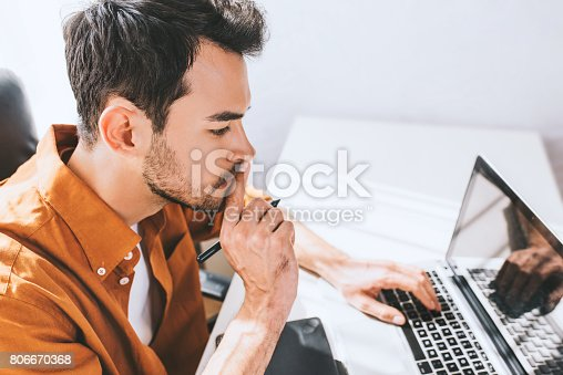 istock Confident male freelancer sitting in front of the computer with serious and thoughtful expression. Young businessman in shirt, with finger on mouth, using pen and laptop for work sitting in the office 806670368