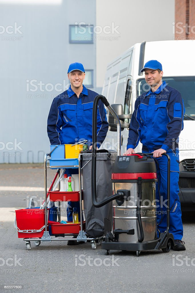 Confident Male Janitors Standing On Street stock photo