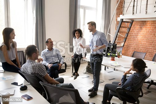 Confident male leader, coach talking with multiracial group of office workers, having good conversation with subordinate, brainstorming, discussing business strategy, ideas, team building activity
