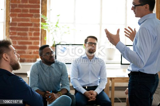 1031235468 istock photo Confident male leader mentor coach speaking at diverse team meeting 1090215718
