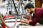 Confident young mechanic adjusting bicycle chain on workbench. Side view of bearded male employee is repairing bike. He is working at sports shop.