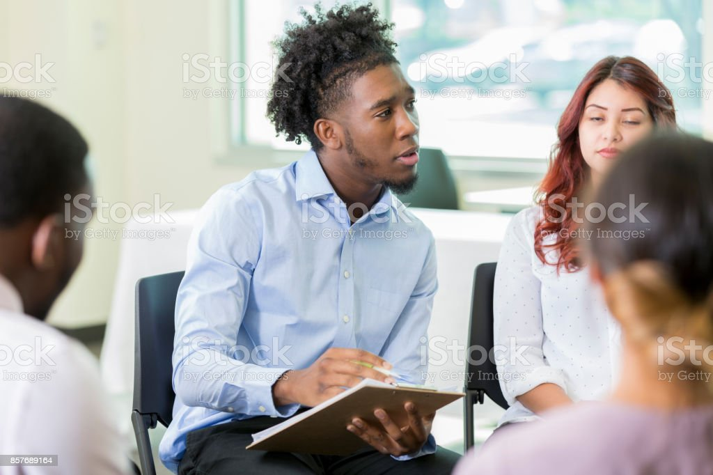 Confident male mental health professional leads support group stock photo