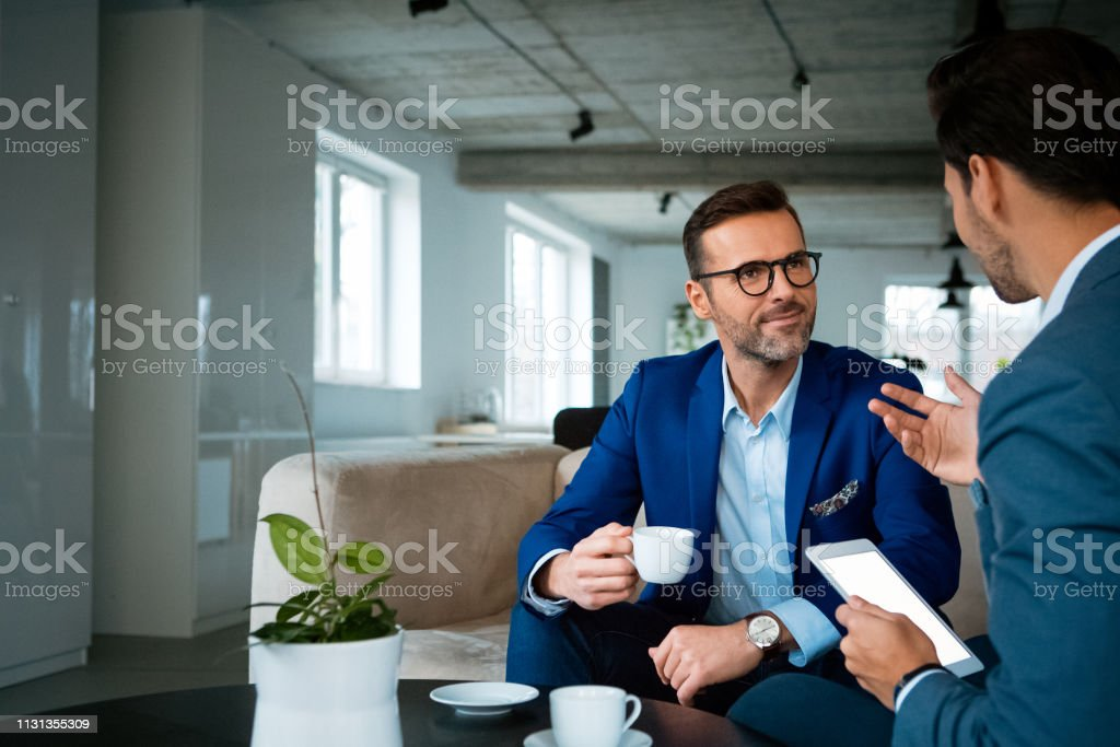 Confident male professionals discussing at office Confident male professionals discussing while sitting at workplace. Businessmen are planning strategy during meeting. They are working at creative office. 30-39 Years Stock Photo