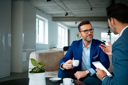 Confident Male Professionals Discussing At Office Stock Photo - Download Image Now