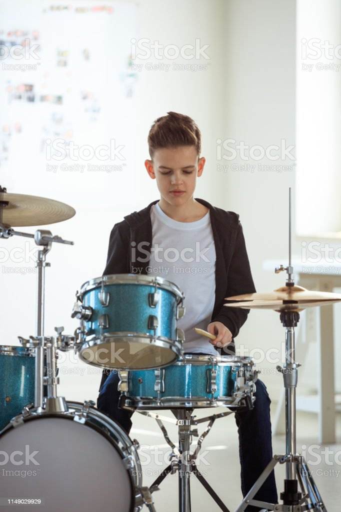 Confident male student practicing drum in class Confident boy playing drum. Pre-adolescent male student is practicing on percussion instrument. He is learning music in conservatory. 12-13 Years Stock Photo