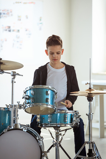 Confident Male Student Practicing Drum In Class Stock Photo - Download Image Now