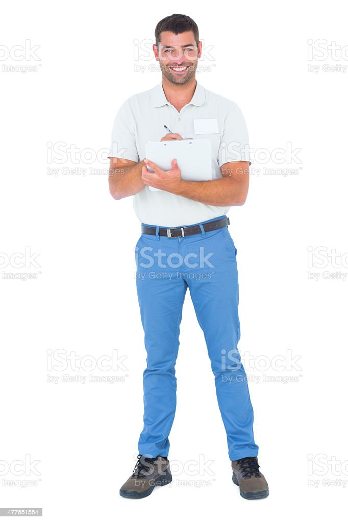 Confident male supervisor writing on clipboard over white background stock photo