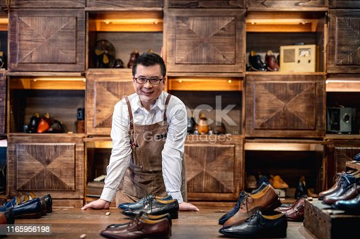 Successful male Taiwanese merchant leaning on a display table featuring high quality dress shoes for men.