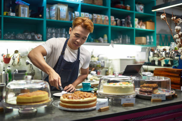 Confident male worker with cake at checkout stock photo