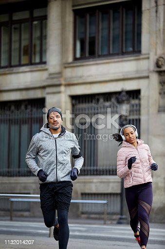 Confident man and woman jogging in city. Full length of couple is running against building. They are in sports clothing at city.