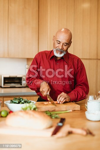 Confident senior man chopping carrot at kitchen island. Retired bald male is preparing meal in kitchen. He is at home.
