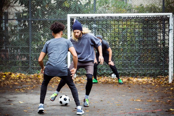 Confident man dribbling ball from opponent Confident young man dribbling ball from opponent. Player is standing at goal post. They are in sportswear. leisure equipment stock pictures, royalty-free photos & images