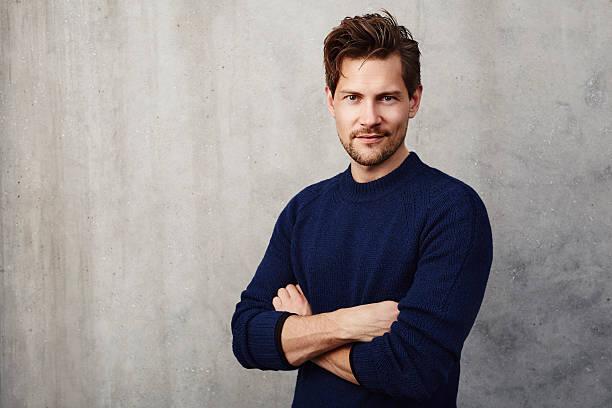 Confident man in blue sweater, portrait stock photo
