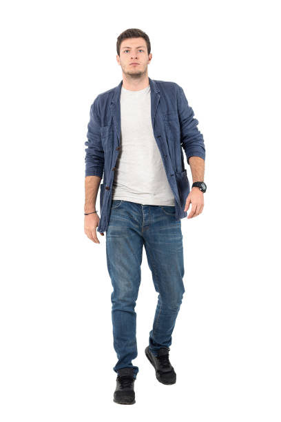 Confident man in denim shirt and jeans walking towards camera Young confident man in denim unbuttoned shirt and jeans walking towards camera. Full body length portrait isolated over white background. approaching stock pictures, royalty-free photos & images