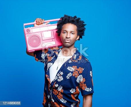 istock Confident man in hawaiian shirt holding pink boom box 1214689033