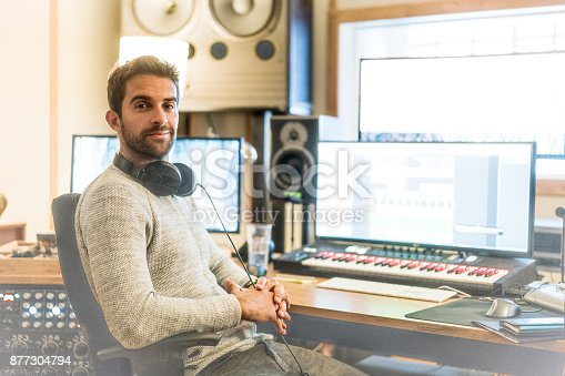 Portrait of confident man sitting on chair in sound recording studio. Record producer is with headphones at workplace. He is wearing casuals.