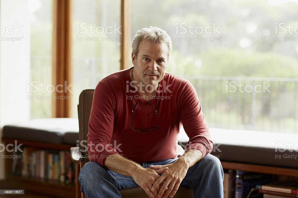 Confident man sitting on armchair at home stock photo