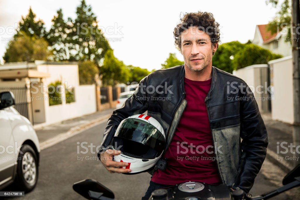Confident man sitting on motorcycle stock photo