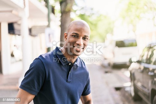 A photo of African American man on sidewalk. Happy young male is wearing polo shirt. Portrait of confident person is standing outside shop.