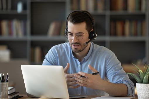 La imagen tiene un atributo ALT vacío; su nombre de archivo es confident-man-teacher-wearing-headset-speaking-holding-online-lesson-picture-id1223044329