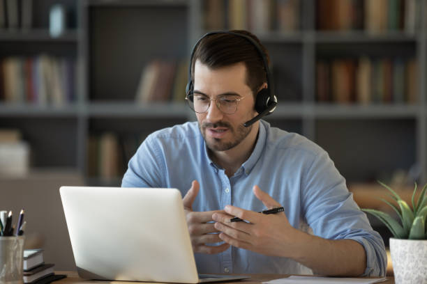 Confident man teacher wearing headset speaking, holding online lesson stock photo