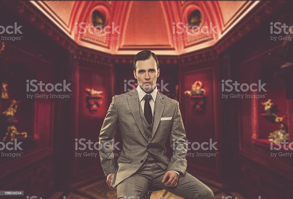 Confident man wearing classic grey suit sitting on chair stock photo