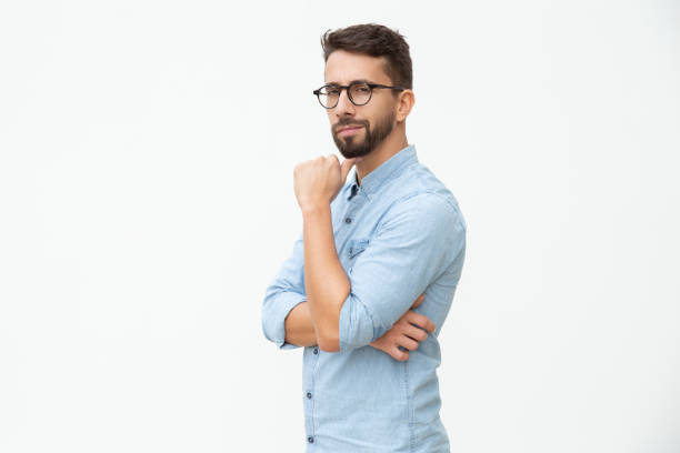 Confident man with hand on chin looking at camera stock photo