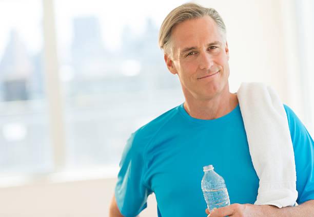 Seguro de hombre con toalla y botella de agua en Club - foto de stock
