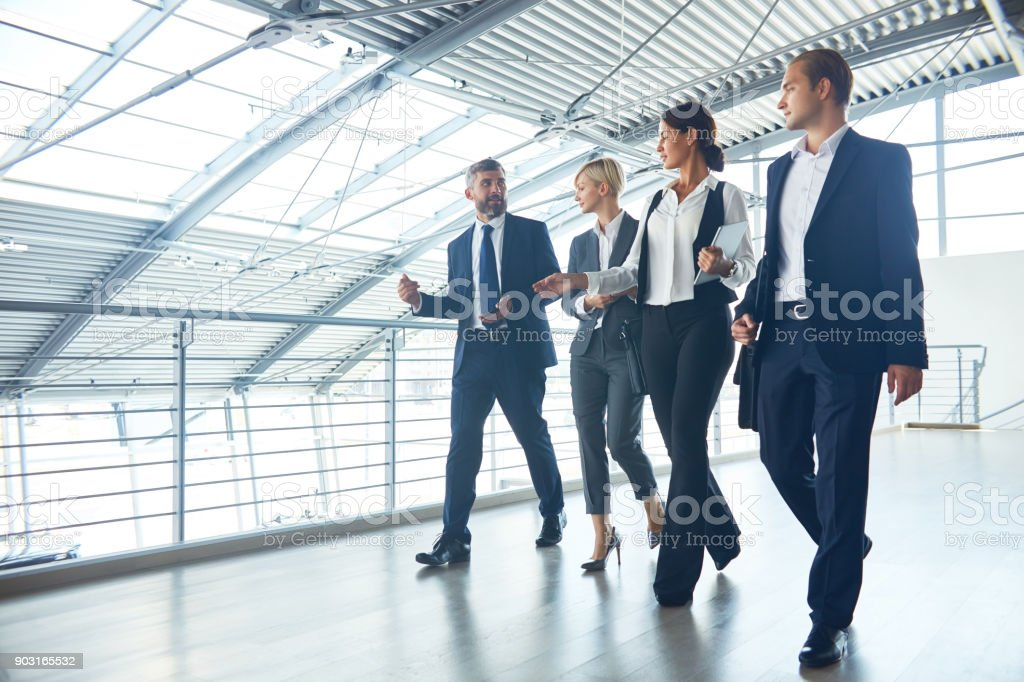 Confident management team talking while walking stock photo