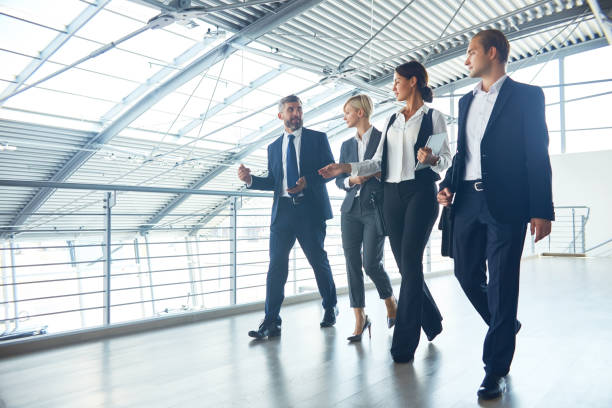 confident management team talking while walking - international moving stock photos and pictures