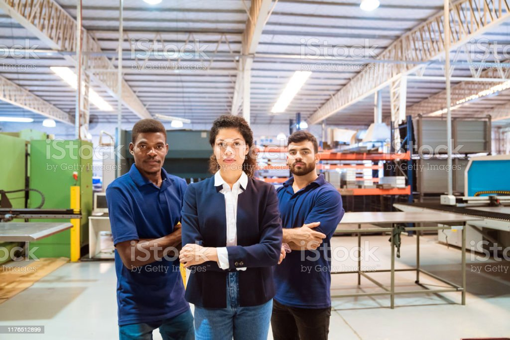 Confident manager and workers in factory Portrait of confident manager and production workers. Expertise are with arms crossed standing in factory. They are related to manufacturing occupation. 20-24 Years Stock Photo