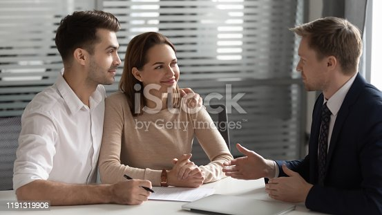 994164754istockphoto Confident manager consulting young couple about contract at meeting 1191319906