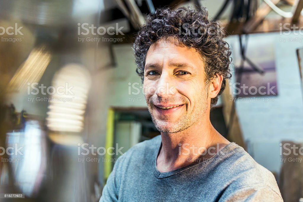 Confident manual worker smiling in workshop stock photo