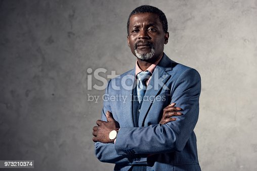 973213156 istock photo confident mature african american man with crossed arms 973210374
