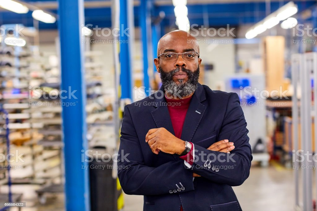 Confident mature african businessman standing in factory stock photo