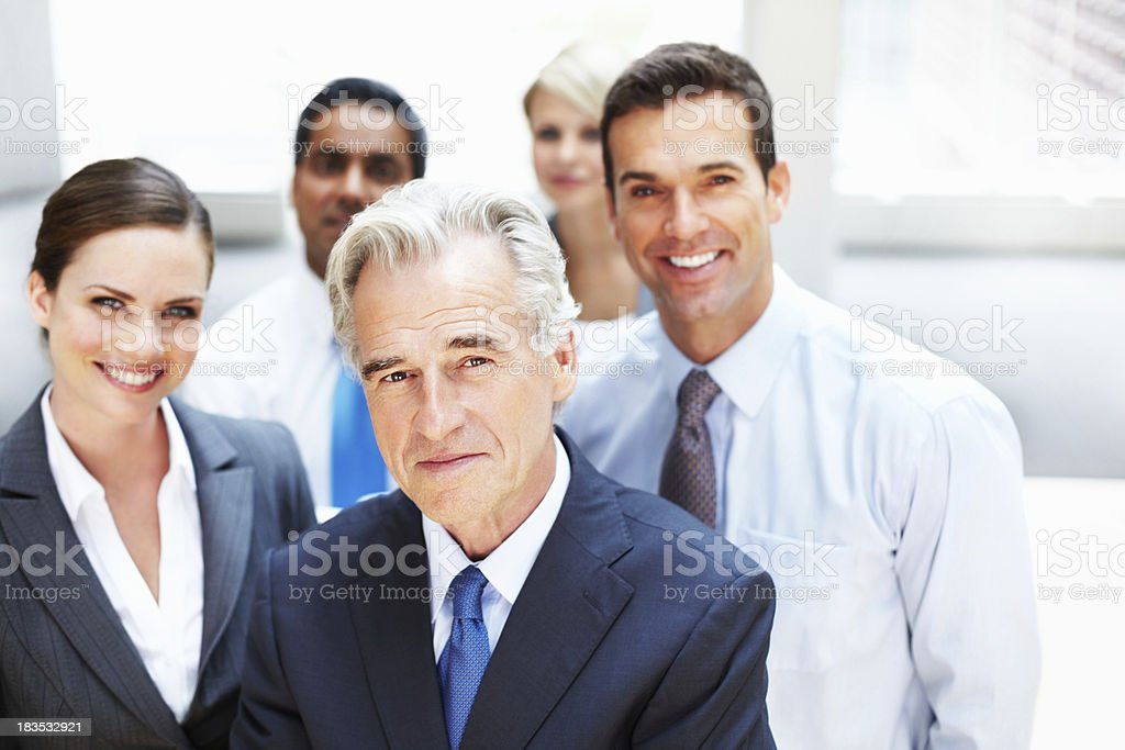 Confident mature business man with his colleagues in background royalty-free stock photo