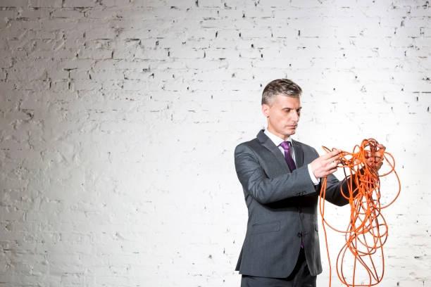 Vertraulich reife Geschäftsmann hält verworrene rote Kabel gegen weiße Backsteinmauer – Foto