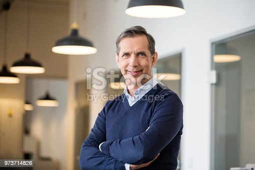 Portrait of a happy mature business professional standing with his arms crossed in modern office. Smiling businessman at his workplace.