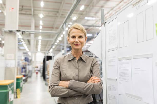 femme d'affaires mature confiant dans l'entrepôt de l'usine grande - directrice photos et images de collection