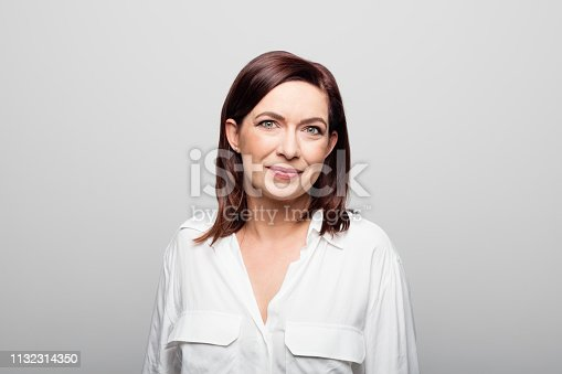 Portrait of confident mature businesswoman. Beautiful female entrepreneur is wearing formals. She is against white background.