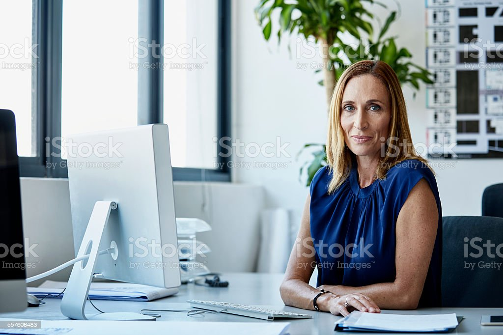 Confident mature businesswoman sitting at desk stock photo