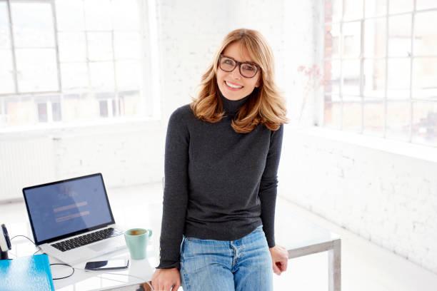 Zuversichtlich, Reife Geschäftsfrau, stehend im Büro beim Blick in die Kamera und lächelnd – Foto