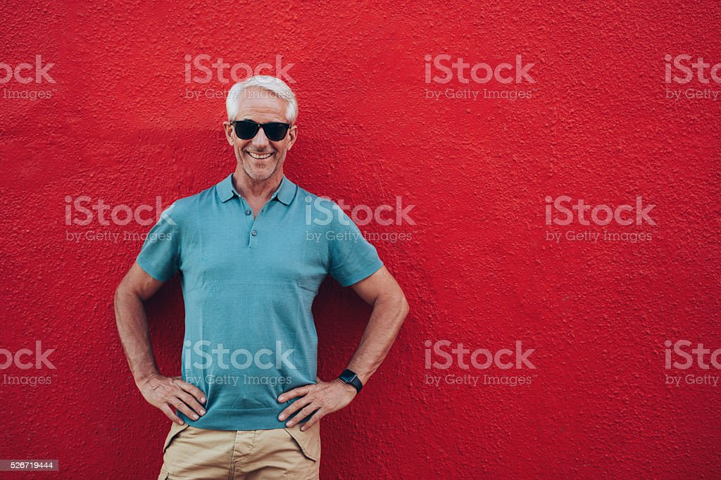 Confident mature man standing on red background stock photo